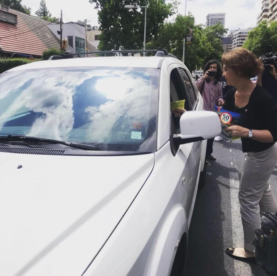 Ministra Hutt entregando volantes de velocidad máxima a automovilistas.